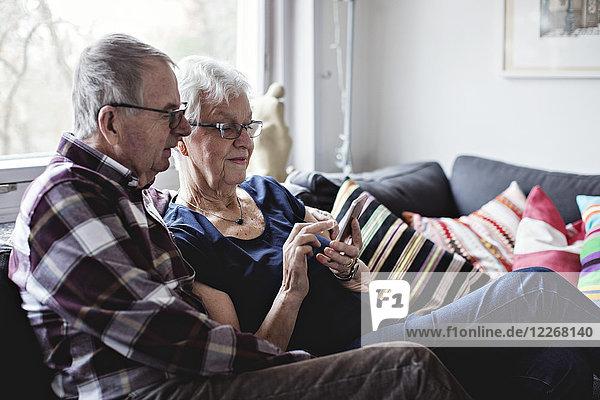 Senioren-Pärchen im Ruhestand teilen sich ein Smartphone auf dem Sofa im Wohnzimmer zu Hause.