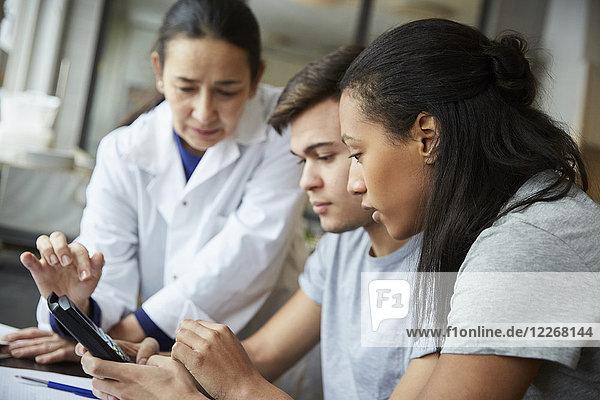 Junge Schülerinnen und Schüler  die den Rechner eines reifen Lehrers im Ingenieurunterricht benutzen.