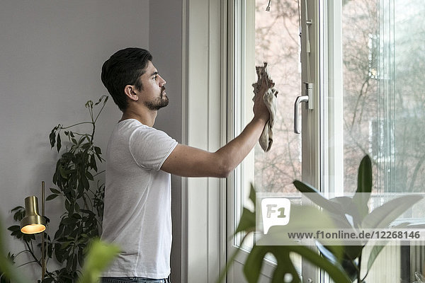 Side view of young man cleaning glass window in living room