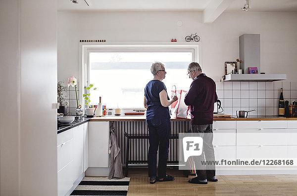 Durchgehende Rückansicht des pensionierten Seniorenpaares in der heimischen Küche