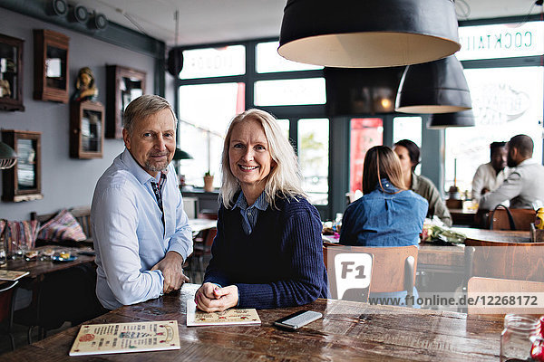 Porträt eines lächelnden reifen Paares mit Menü am Holztisch gegen Menschen im Restaurant