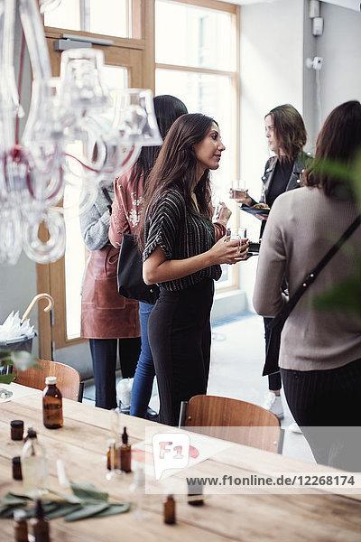 Multiethnische Mitarbeiterinnen stehen am Tisch in der Parfumwerkstatt Multiethnische Mitarbeiterinnen stehen am Tisch in der Parfumwerkstatt