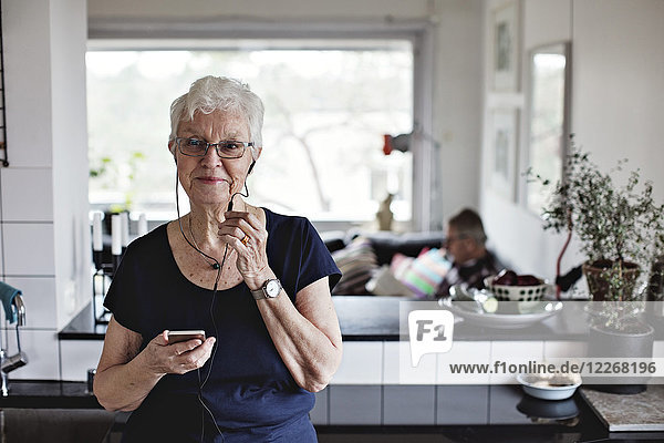 Confident senior woman holding smart phone while listening to in-ear headphones in kitchen at home