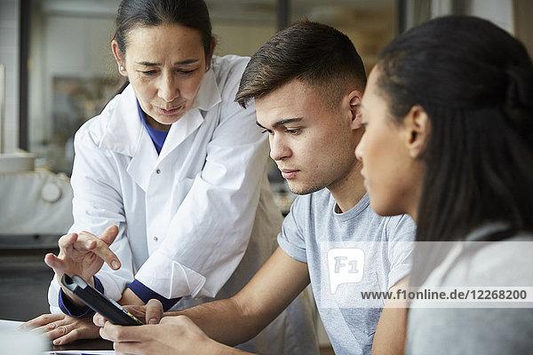 Reife Lehrerin mit jungen Schülern mit Taschenrechner im Technikunterricht