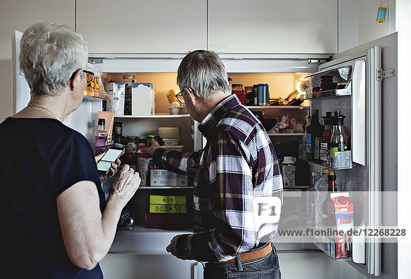 Seniorenpaar steht neben Kühlschrank in der Küche zu Hause