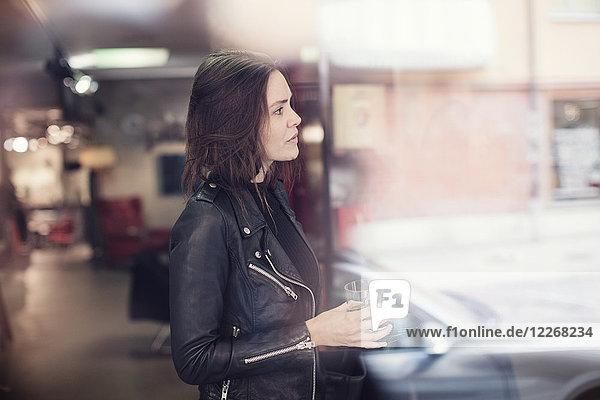 Seitenansicht der Frau in schwarzer Lederjacke mit Getränk im Stehen in der Werkstatt vom Fenster aus gesehen