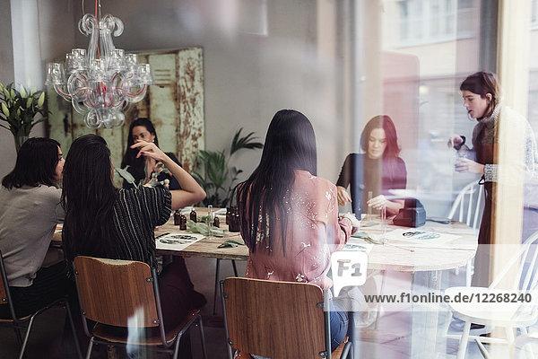 Multi-ethnische Kollegen bei der Zubereitung von Parfüm am Tisch in der Werkstatt vom Fenster aus gesehen