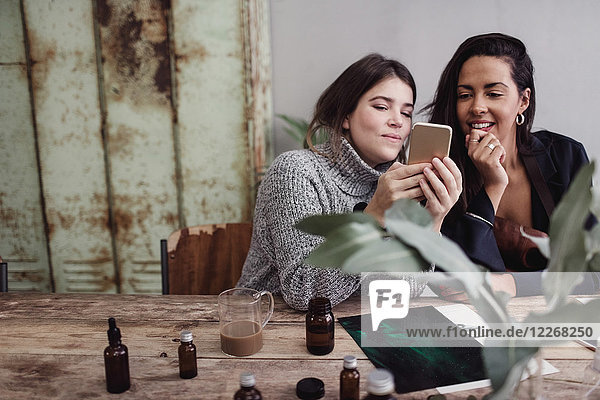 Smiling woman sharing smart phone with female colleague while sitting at table in perfume workshop