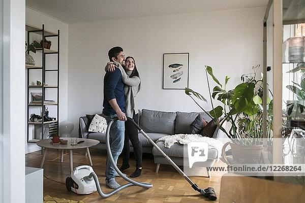 Ein glückliches Paar  das sich beim Putzen des Wohnzimmers umarmt.