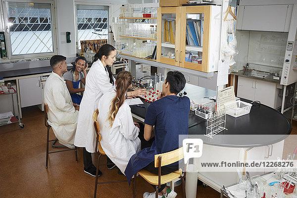 Mature teacher explaining to young multi-ethnic university students sitting in chemistry laboratory
