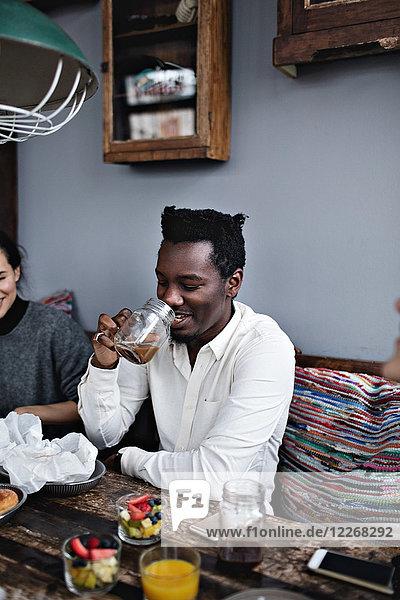 Lächelnder junger Mann beim Trinken mit Freundin im Restaurant