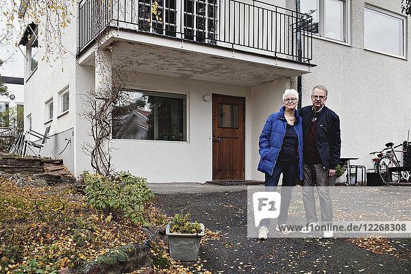 Porträt eines pensionierten Seniorenpaares  das gegen das Haus steht.