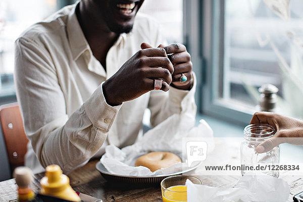 Mittelteil des Mannes mit Freund beim Brunch am Tisch im Restaurant