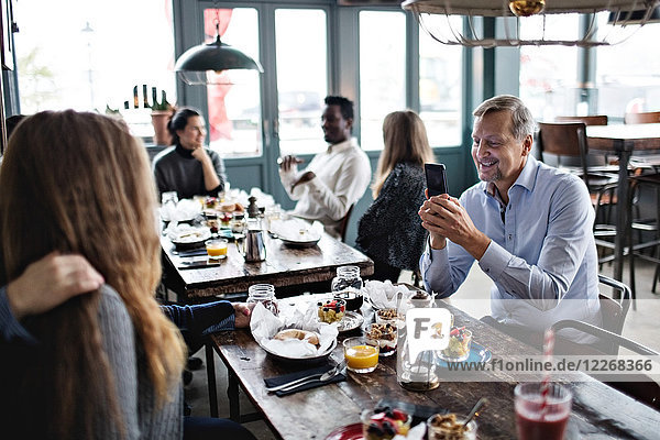 Man photographing women while friends sitting at table in restaurant