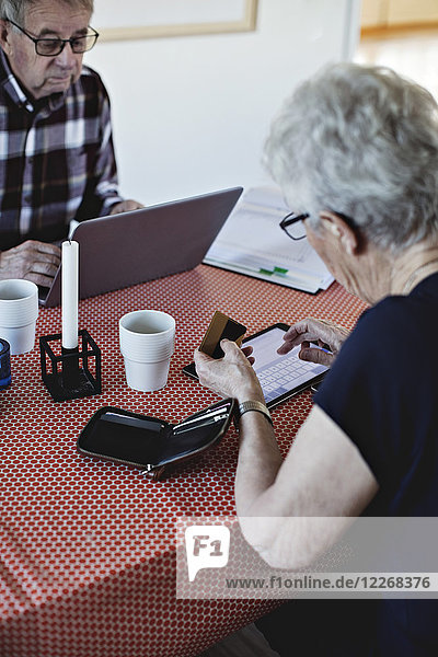 Senior woman holding credit card while using digital tablet at dining table