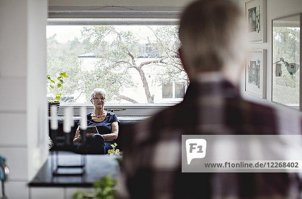 Rückansicht des älteren Mannes mit Blick auf die Frau auf dem Sofa im Wohnzimmer