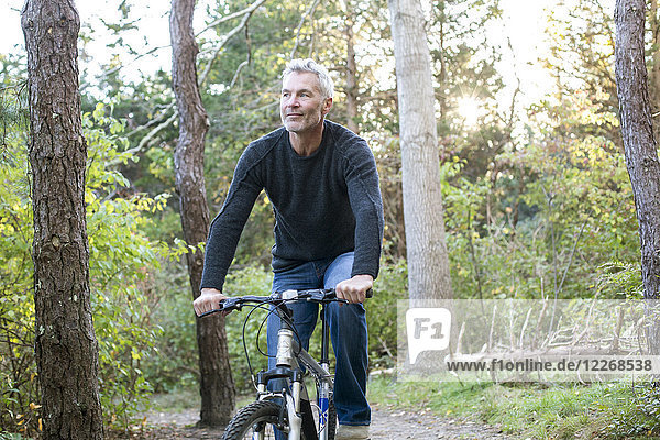 Gray-haired man riding bicycle in forest  Massachusetts  USA
