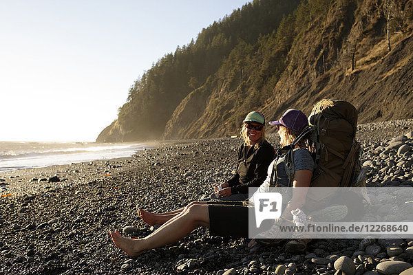 Hikers resting at beach at sunset while hiking Lost Coast Trail  Kings Range National Conservation Area  California  USA