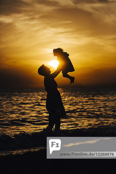 Silhouette of mother and daughter playing on beach at sunset  Side  Turkey