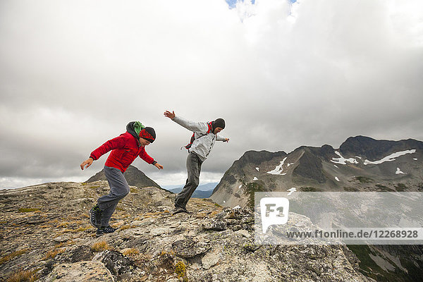 Two hikers battling strong wind on rocky ridge  Merritt  British Columbia  Canada