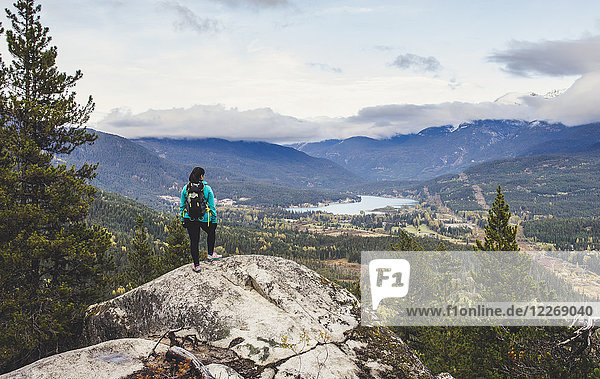 Female hiker looking at view of Whistler and Green Lake from lookout along Flank Trail  British Columbia  Canada
