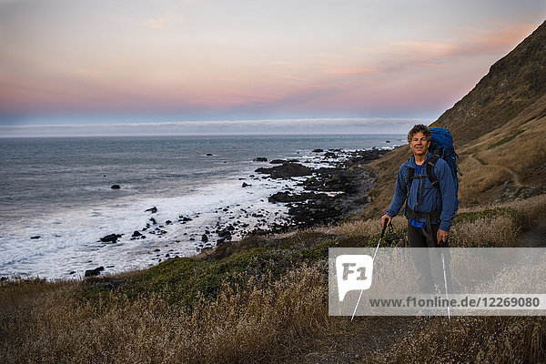 Male backpacker standing with trekking poles at shore of Lost Coast at dusk  California  USA
