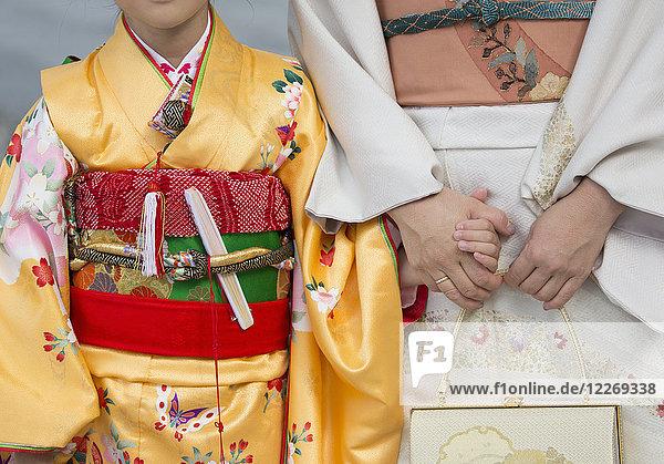Nahaufnahme einer Frau und eines Kindes,  die sich an den Händen halten,  in traditionellen japanischen Kimonos nebeneinander stehen und Smartphones halten.