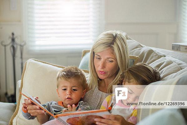 Mittlere erwachsene Frau liest mit Tochter und Kleinkind Sohn auf dem Sofa