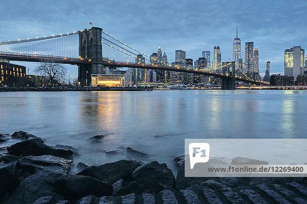 Cityscape with Brooklyn Bridge and Lower Manhattan skyline at dusk  New York  USA