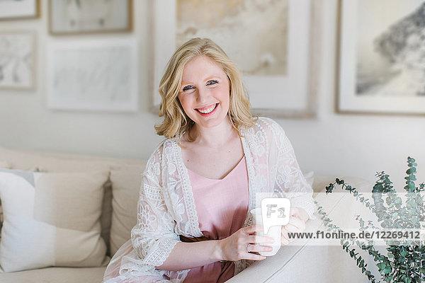 Junge Frau sitzt auf Sofa und hält Kaffeetasse  Porträt
