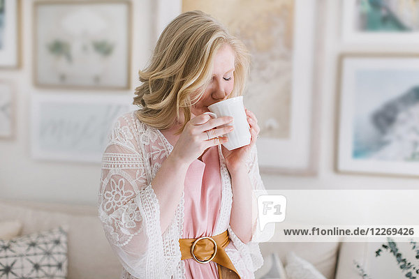 Young woman in living room drinking coffee
