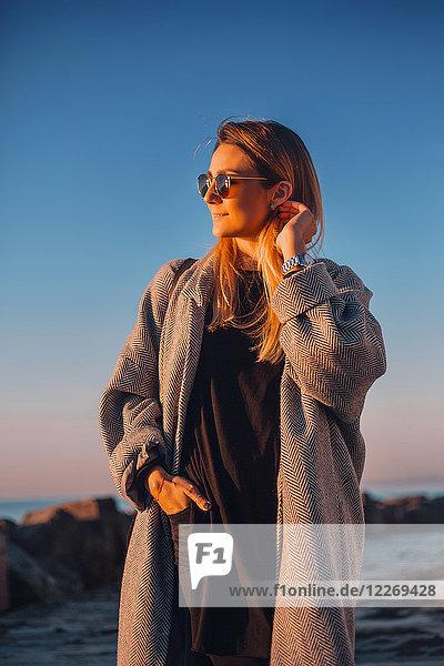 Porträt einer Frau mit Sonnenbrille und Wintermantel beim Wegschauen  Odessa  Odeska Oblast  Ukraine  Osteuropa