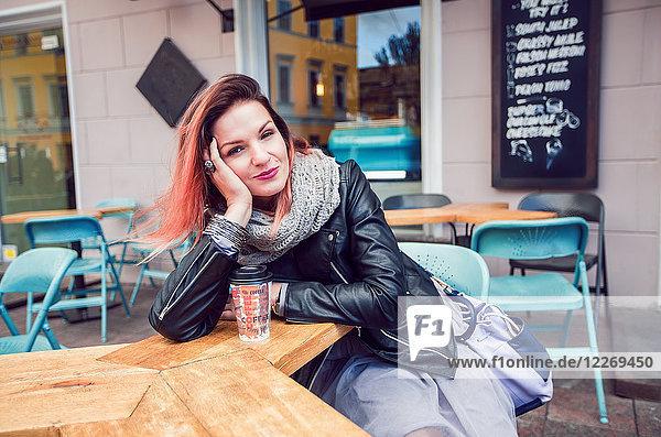 Frau sitzt am Tisch im Straßencafé