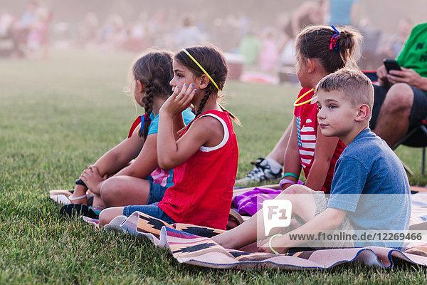 Gruppe von Erwachsenen und Kindern  im Freien sitzend  während der Feierlichkeiten zum 4. Juli
