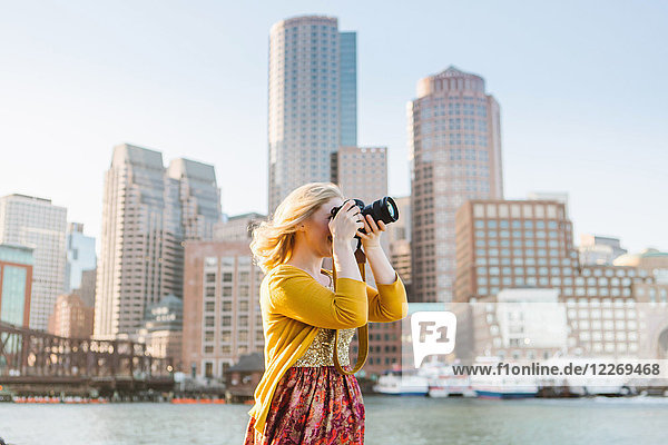 Young female photographer photographing from quayside  Boston  Massachusetts  USA