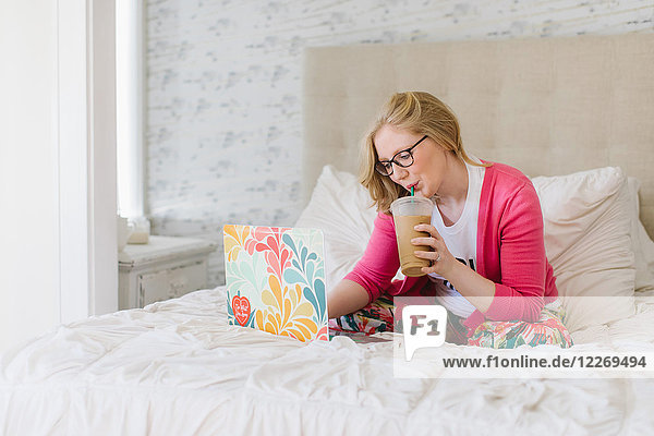 Young woman sitting on bed drinking takeaway coffee and using laptop