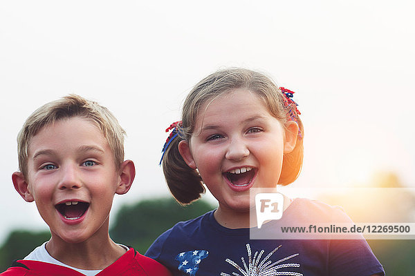 Portrait of boy and girl  mouths open  smiling  looking at camera