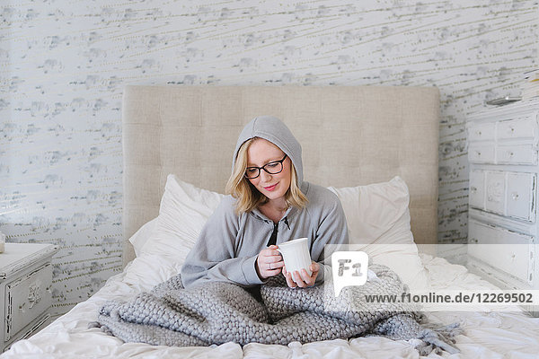 Young woman wrapped in blanket sitting on bed with cup of coffee