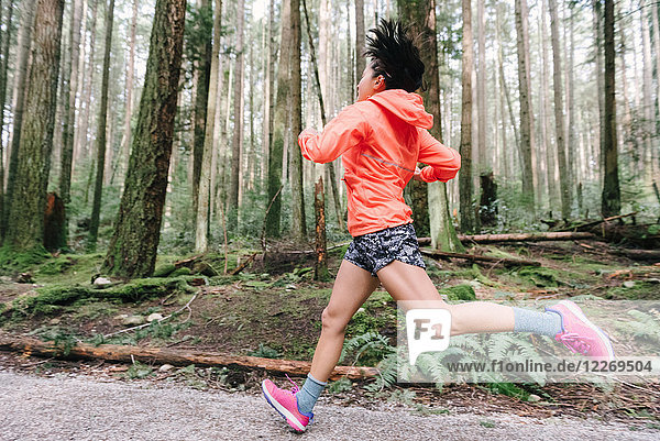 Woman running in forest  Vancouver  Canada