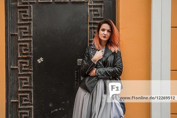 Porträt einer Frau an einer verzierten Tür mit Blick in die Kamera