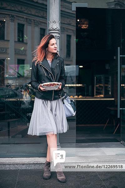 Porträt einer Frau auf der Strasse  die einen Teller mit Essen in der Hand hält