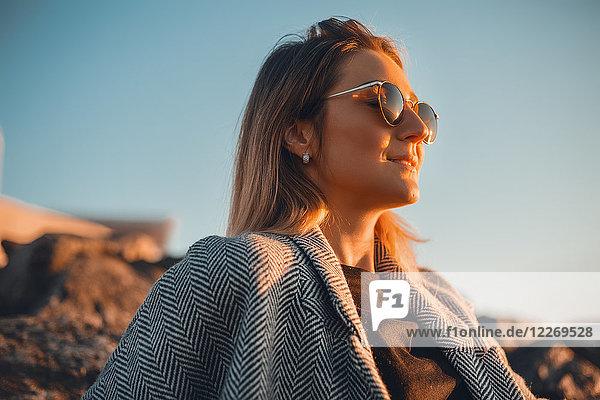 Porträt einer Frau mit Sonnenbrille  die lächelnd wegschaut