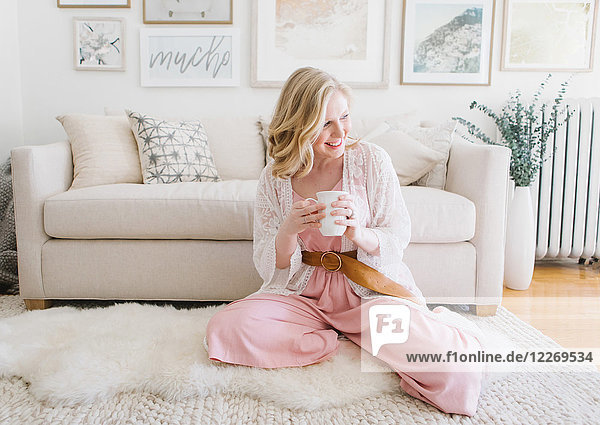 Junge Frau sitzt mit Kaffee auf dem Wohnzimmerboden