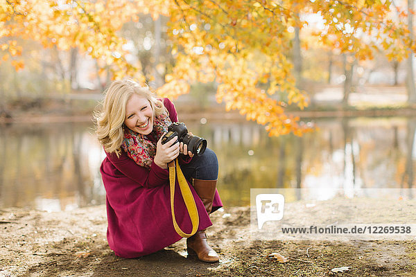 Young woman crouching to take photographs with DSLR camera in autumn park