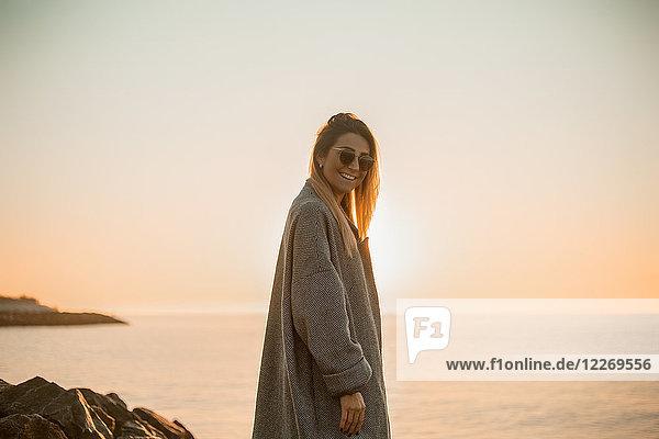 Porträt einer Frau mit Sonnenbrille und Wintermantel  die lächelnd in die Kamera blickt  Seitenansicht  Odessa  Odeska Oblast  Ukraine  Osteuropa