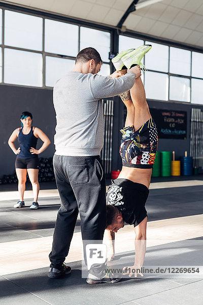 Mann im Fitnessstudio hilft Freund beim Handstand