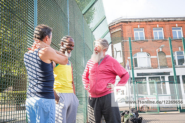 Drei reife Männer auf dem Basketballplatz  die zusammen lachen