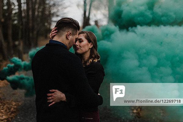 Junges Paar küsst sich im Wald bei grüner Rauchwolke