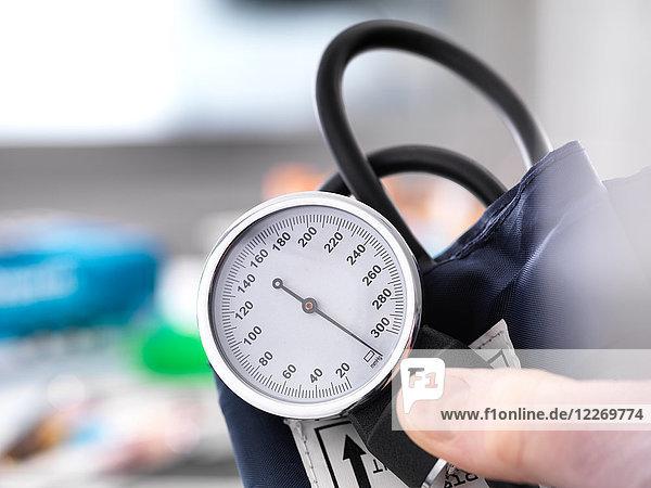 Schrägansicht eines Arztes  der ein Blutdruckmessgerät hält