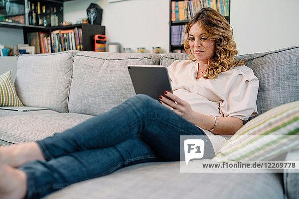 Schwangere Frau auf Sofa schaut auf digitales Tablett